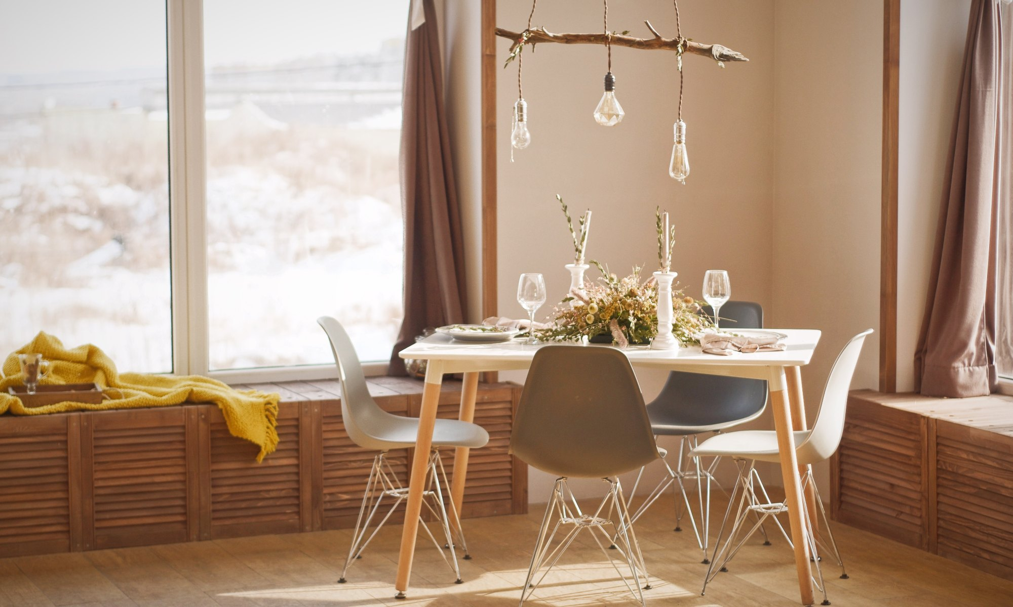 Small dining table and chairs in a corner beside a window