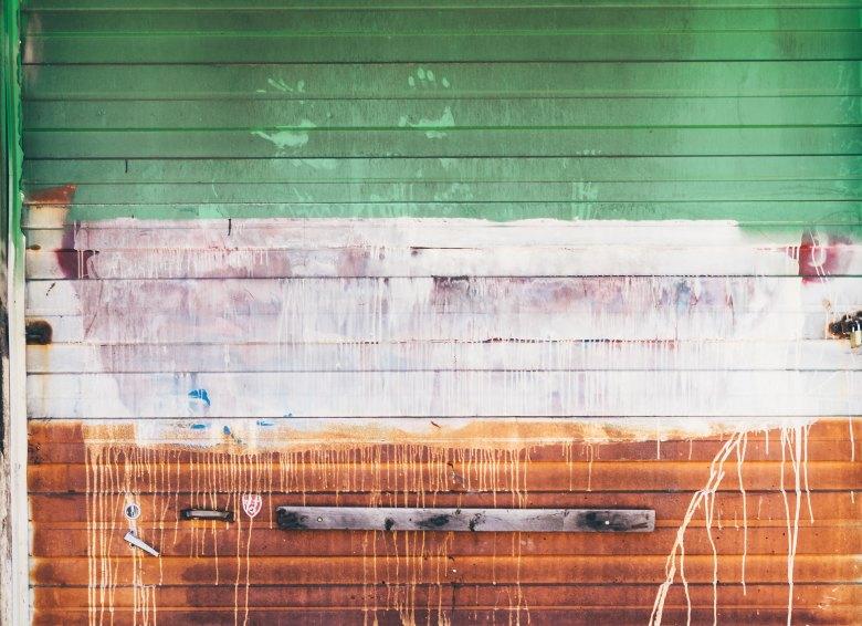 Rusty garage door splashed with white paint