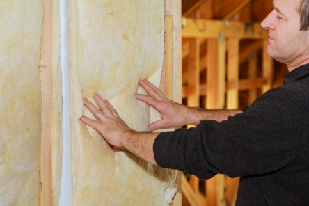 Man laying thermal insulation layer under the roof using mineral wool panels, installation of insulation in the house, insulation of the house