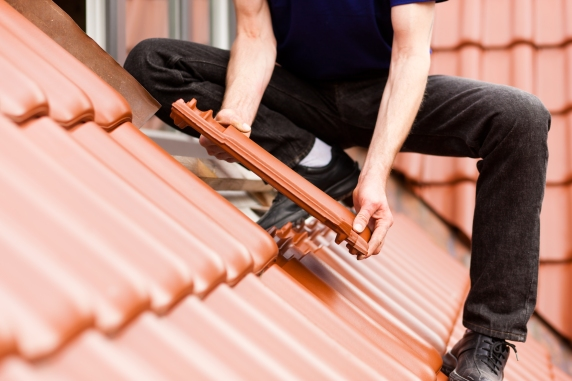 Roofing, construction worker standing on a roof covering it with tiles