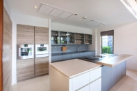 Organized kitchen, white walls, gray counter tops, and wooden cupboards